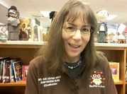 picture of elementary school librarian sitting in front of book shelves